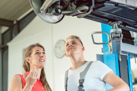 Experienced mechanic standing next to a female customer, while looking worried at the old suspension system of a lifted car in a modern automobile repair shop