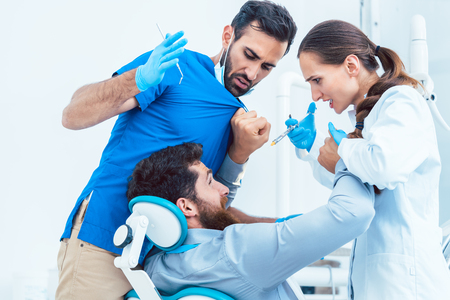 Low-angle view of a funny dentist or dental surgeon acting crazy in front of his female assistant, while having a patient on the chair in the dental office