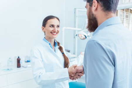 Portrait of a reliable and cheerful female dentist or dental surgeon shaking the hand of a patient in the dental office of a modern clinic