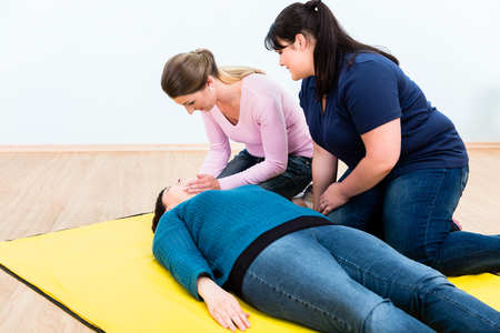 Women in first aid class training to position injured person