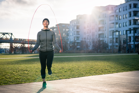 Full length of a young fit woman burning calories through alternate jumping over the skipping rope outdoors in a sunny day in the park Archivio Fotografico