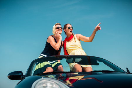 Woman having summer trip in convertible car stretching hands in the air with fun