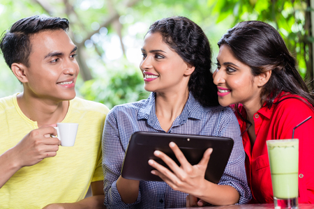 Group of young Indians looking at tablet computer while sitting in cafe Stock Photo