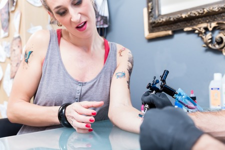 Close-up of the hand of a creative tattoo artist shading a colorful butterfly on the forearm of a female client in a modern studio Stock Photo