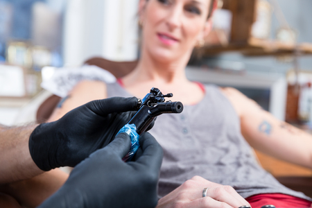 Close-up of the hands of a tattoo artist wearing black sterile gloves while preparing a professional machine for tattooing a female client
