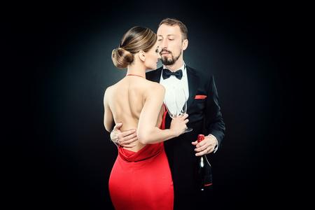 Elegante pareja en traje de noche abrazándose en el amor celebrando en una fiesta con clase