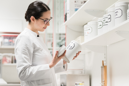 Side view of an experienced female pharmacist checking the container of a chemical pharmaceutical substance during inventory in a modern drugstore