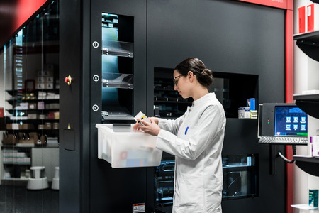 Vista posterior de ángulo bajo de una farmacéutica experimentada que usa una computadora mientras administra el stock de medicamentos en una farmacia contemporánea con tecnología moderna
