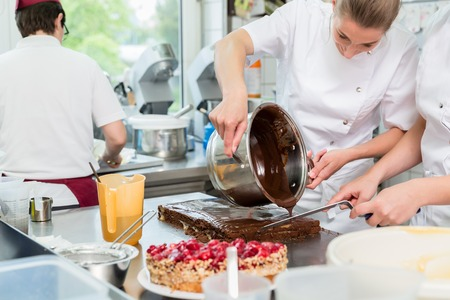 Confectioner or Patissier putting chocolate as frosting on cake