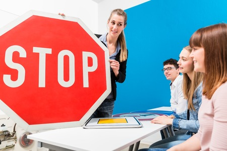 Driving teacher explaining meaning of street signs to class of students Archivio Fotografico