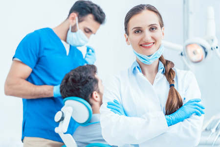 Portrait of a happy and confident female dentist wearing sterile white coat and surgical gloves, while looking at camera in the dental office of a modern clinic with reliable specialists