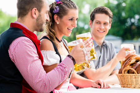 People with beer and pretzel in Bavarian inn eating and drinking Stock Photo