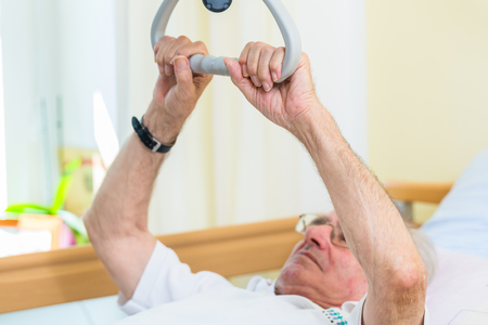 Senior man grabbing handle to get out of bed in nursing home Stock Photo