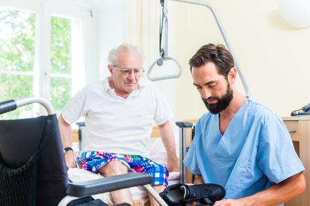 Elderly care nurse helping senior from bed to wheel chair in hospital or nursing home Standard-Bild - 98167080