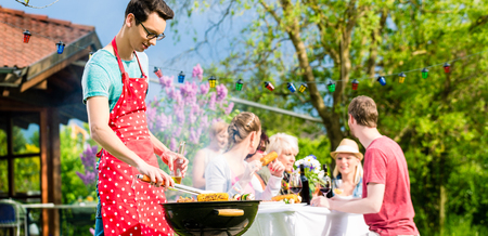 Man grilling meat on garden barbecue party, in the background friends eating and drinking Standard-Bild - 103214391