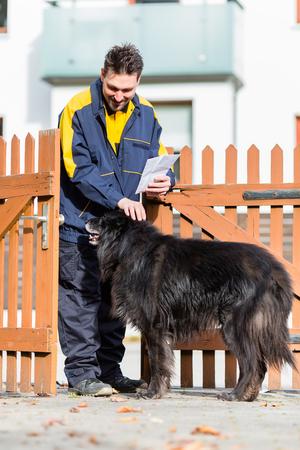 Big black dog welcoming the postman at garden gate Stock Photo