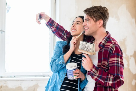 Young couple in love making a funny selfie while working together to the interior renovation of their new home Stock Photo