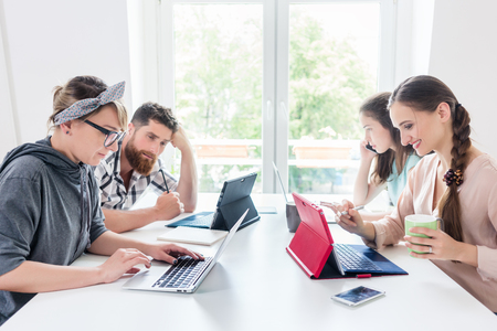 Dedicated young woman editing a document on laptop, while sharing the desk with other hard-working co-workers in a modern office space for digital nomads
