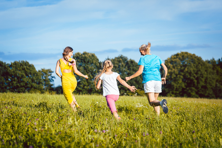 Two women and girl playful on a summer meadow running Reklamní fotografie