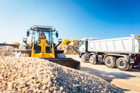Trabajadores de la construcción haciendo movimientos de tierra con cargadora de ruedas y camión de escombros
