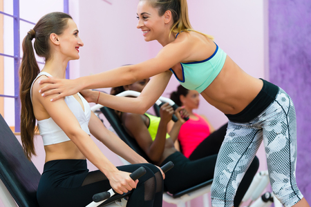 Side view of a qualified female fitness instructor helping a cheerful young woman to straighten her back while exercising the arm muscles at gym