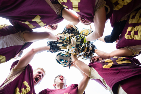 American Football Team players huddle after their victory