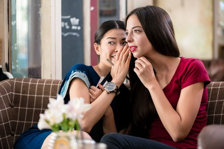 Young woman whispering gossip or sharing a secret with her best friend