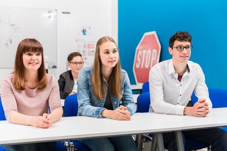 Schüler im Fahrunterricht hören aufmerksam auf Bänken zu Standard-Bild