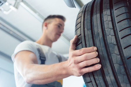 Low-angle view of the hand of a skilled auto mechanic holding a new high-quality tire during work in a modern automobile repair shop Stock Photo