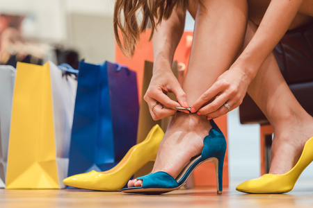 Woman trying to fit new shoes she wants to buy in store Stock Photo