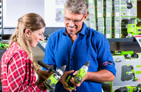 Clerk in electric goods department of hardware store shows several cordless screwdrivers to customer