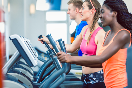 Side view of a fit happy woman and her training group on treadmill in the gym Stock Photo