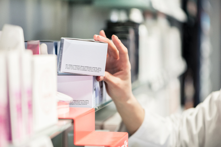 Close-up side view of the hand of a female pharmacist, picking up the package of the best pharmaceutical product from the shelf in a contemporary drugstore Foto de archivo