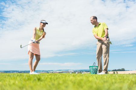 Full length of a young woman smiling while practicing the correct move for striking during golf class with a skilled professional player outdoors Stock Photo