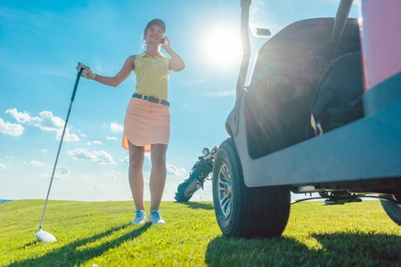 Full length of an active and cheerful woman wearing modern golf apparel, while talking on mobile phone on the golf course near the cart in a sunny day of summer Stock Photo