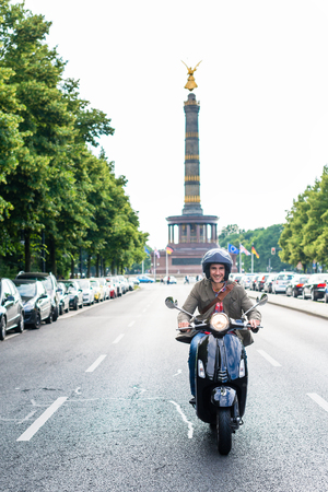 Tourist in Berlin riding scooter in dense traffic Stock Photo