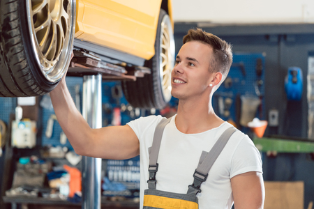 Portrait of a car tuning specialist smiling, while checking the wheels of a tuned lifted car with cool modified rims in a trendy automobile repair shop