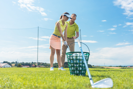 Full length of a cheerful young woman learning the correct grip and move for using the iron golf club, under the guidance of a skilled male teacher outdoors in summer