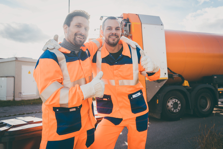 Garbage removal workers giving a thumbs-up in front of disposal truck Stock Photo