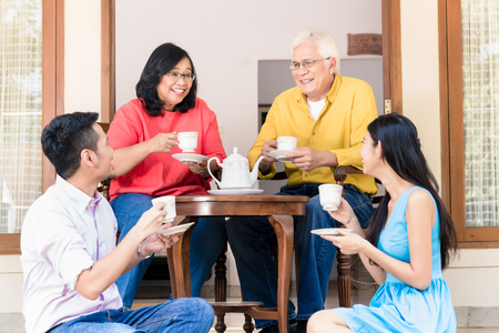 Side view of young man and woman visiting parents at home in the afternoon at tea time Stockfoto