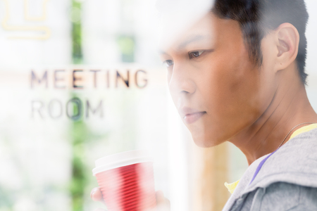 Portrait of creative young Asian employee smiling while thinking of innovative business ideas in the meeting room