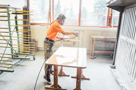 Woman carpenter spraying varnish on a table she works on in her workshop