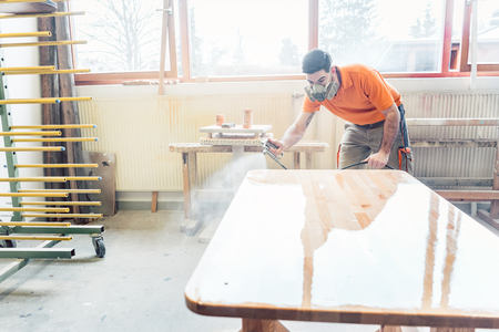 carpenter man spraying varnish on a table he works on using breathing protection