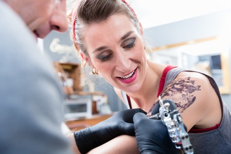 Portrait of a cheerful fashionable woman smiling while looking at the tattoo artist with confidence in a modern studio with sterile professional equipment