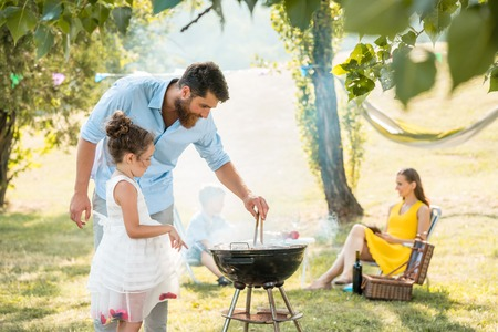 Side view of a cute girl watching her father preparing meat on a round charcoal barbecue grill outdoors during family picnic in a summer day Stock Photo