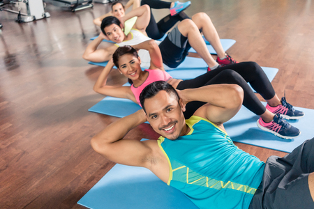Handsome young man smiling and looking at camera while exercising lateral crunch on mat during group workout class at the gym