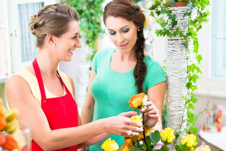 Florist woman selling rose bouquet to her female customer Stock Photo