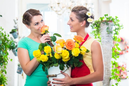 Women in flower store enjoying the roses sniffing at them Stock Photo