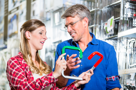 Young woman asking shop assistant in ironware department of hardware store about mountings for window boxes Stock Photo