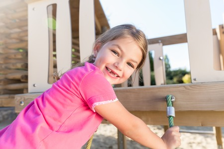 Little girl climbing on adventure playground already lost some teeth Imagens - 99975133